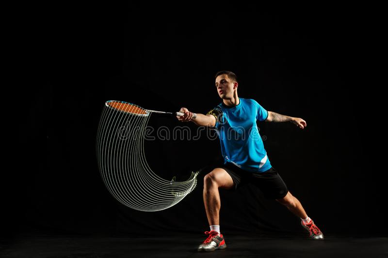 Young male badminton player over balck background. Young man playing badminton over black studio background. Fit male athlete isolated on dark with led light stock image