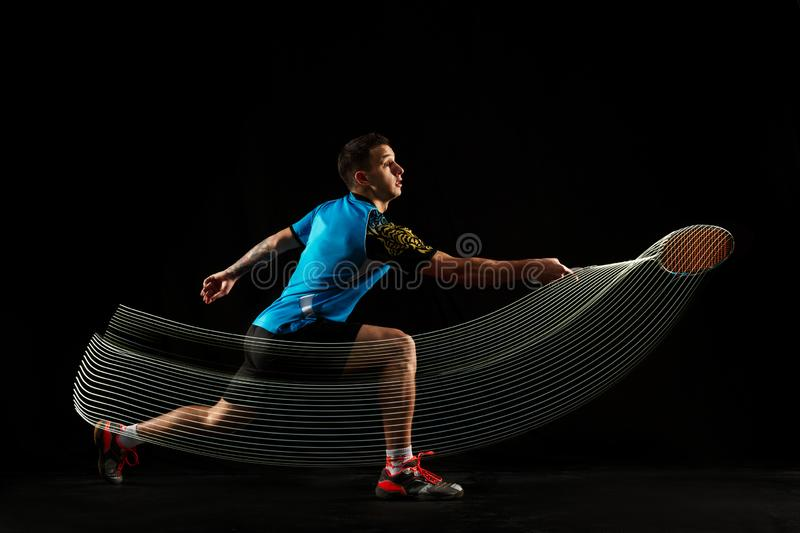 Young male badminton player over balck background. Young man playing badminton over black studio background. Fit male athlete isolated on dark with led light stock photo