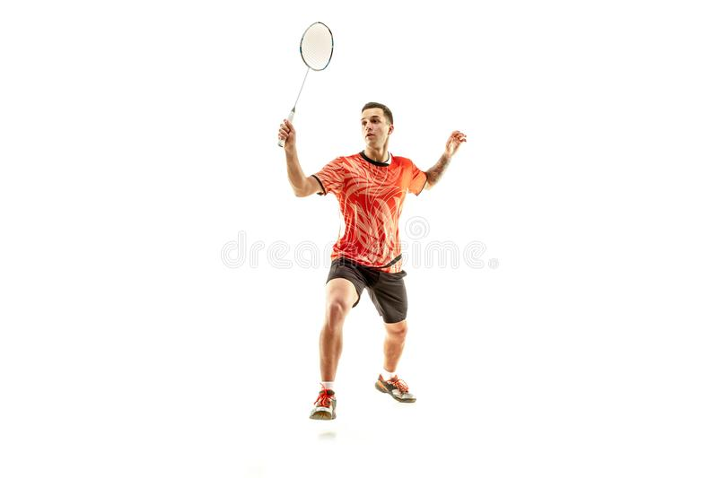 Young male badminton player over white background. Young man playing badminton over white studio background. Fit male athlete isolated on white. badminton player royalty free stock photo