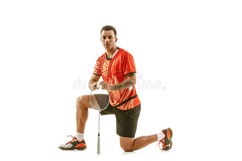 Young male badminton player over white background. Young man playing badminton over white studio background. Fit male athlete isolated on white. badminton player royalty free stock images