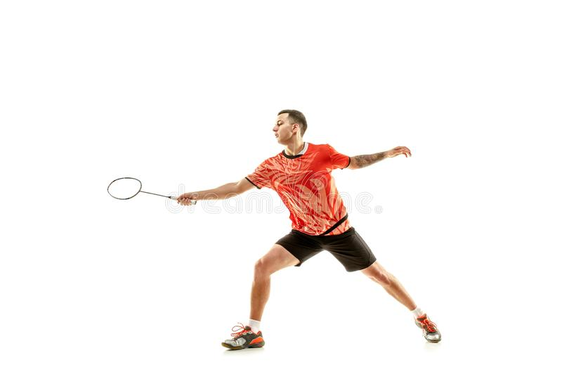 Young male badminton player over white background. Young man playing badminton over white studio background. Fit male athlete isolated on white. badminton player royalty free stock photography