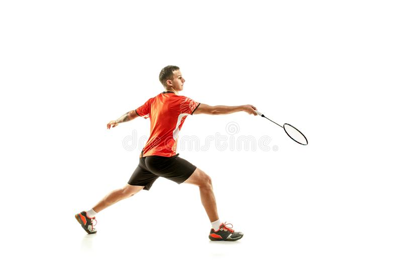 Young male badminton player over white background. Young man playing badminton over white studio background. Fit male athlete isolated on white. badminton player royalty free stock image
