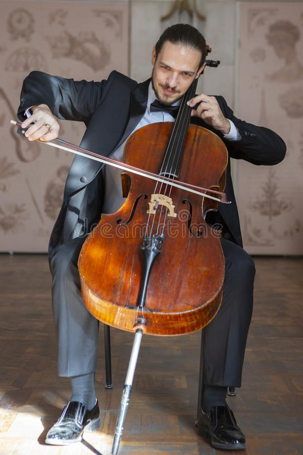 Young man playing the cello. Portrait of the cellist stock photo