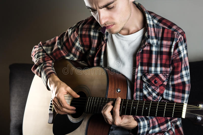 Young man playing chord on guitar royalty free stock photography