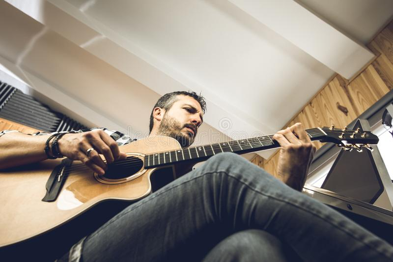 Young man playing classical guitar in studio. Musician guitarist. Young man playing classical guitar in studio.Concept of musician guitarist royalty free stock images