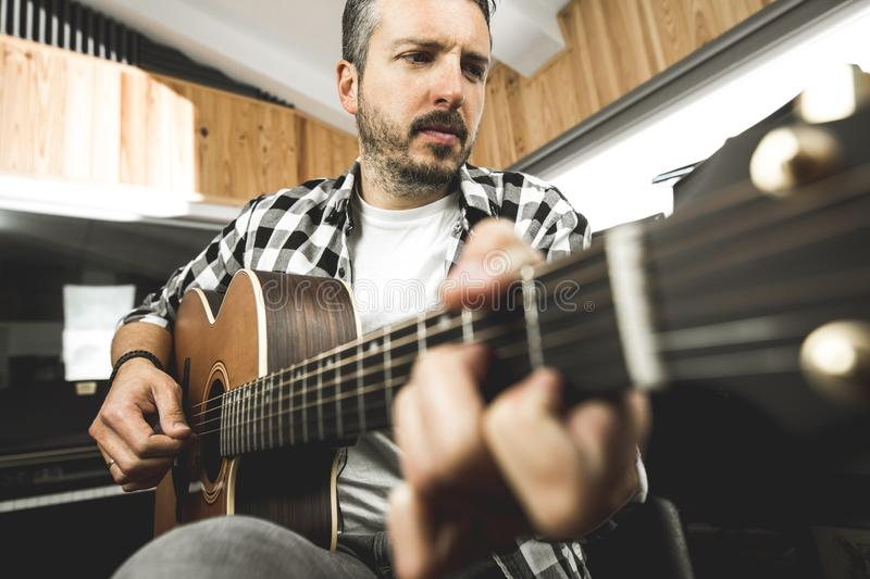 Young man playing classical guitar in studio. Musician guitarist. Young man playing classical guitar in studio.Concept of musician guitarist stock photography