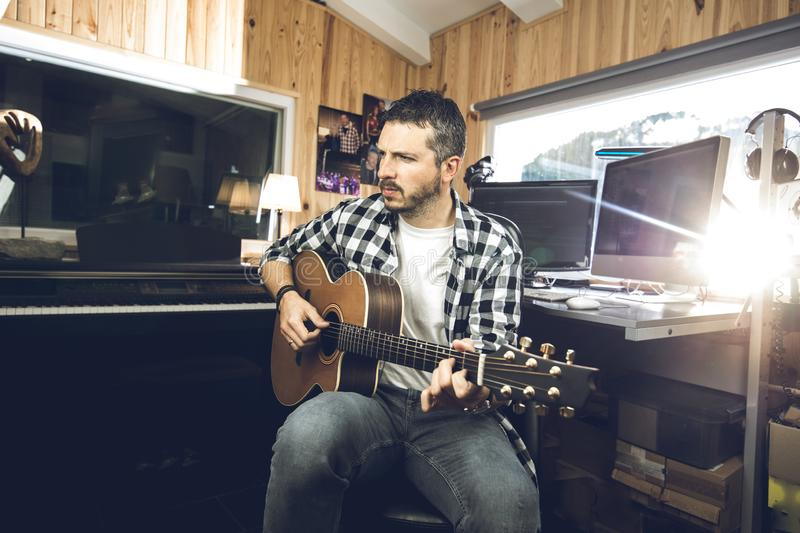 Young man playing classical guitar in studio. Musician guitarist. Young man playing classical guitar in studio.Concept of musician guitarist stock images