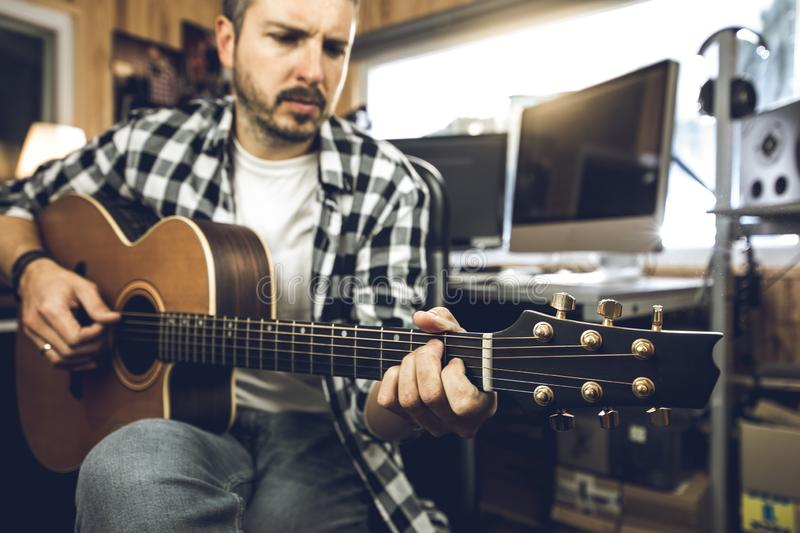 Young man playing classical guitar in studio. Musician guitarist stock photography