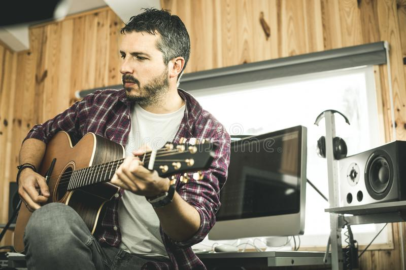 Young man playing classical guitar in studio. Musician guitarist. Young man playing classical guitar in studio.Concept of musician guitarist royalty free stock photos