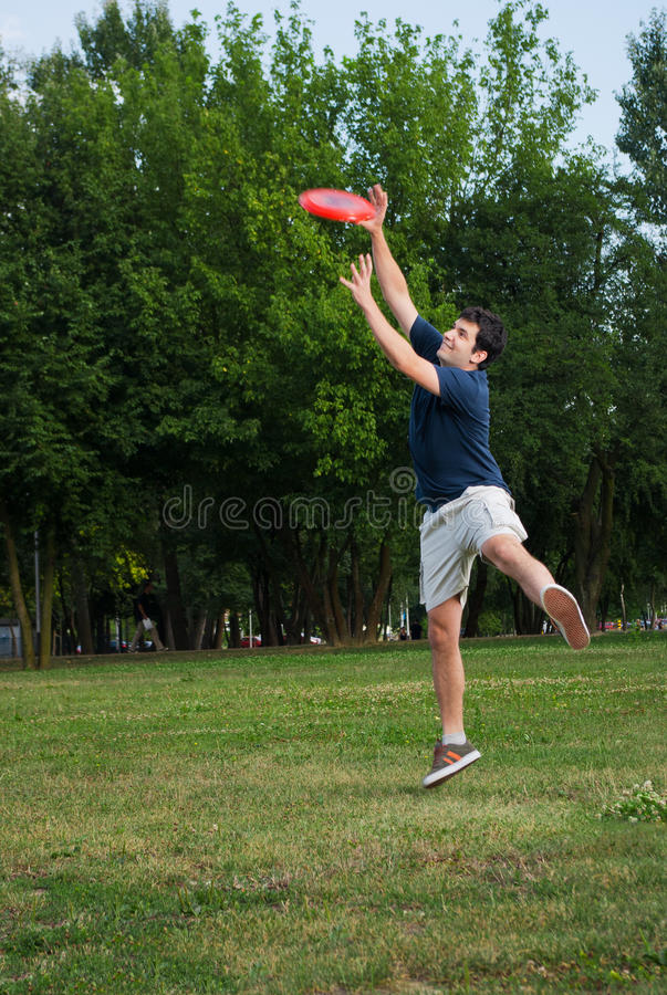 Young man playing frisbee outdoors royalty free stock photos