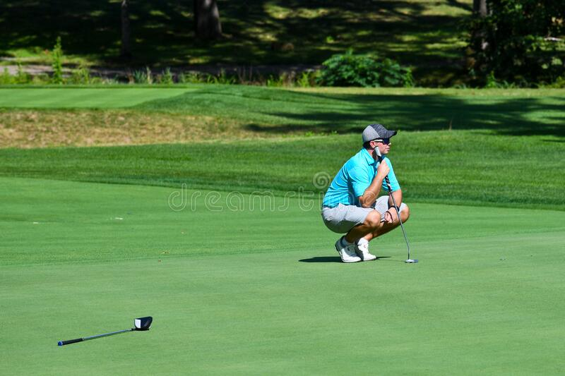 Young Kneeling While Man Playing Golf stock photo