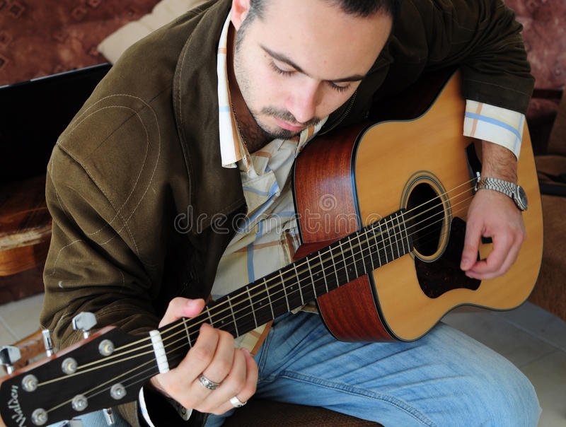 Young man playing the guitar royalty free stock photography