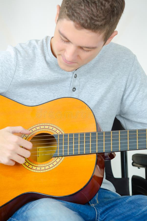 Young man playing guitar and composing song. Young man playing guitar and composing a song stock image