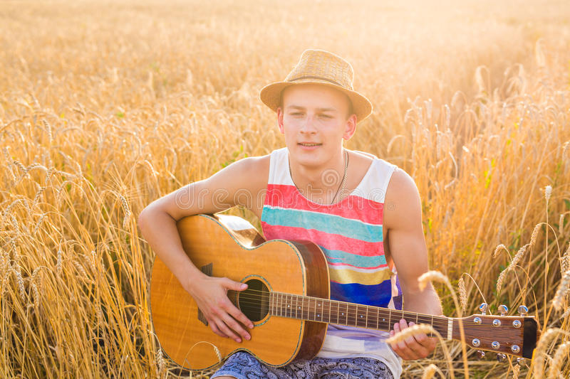 Young man is playing guitar in the field.  stock images