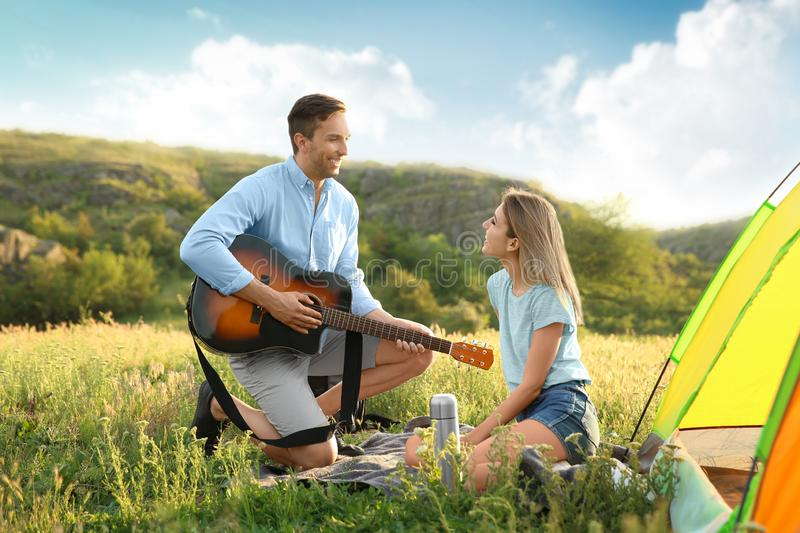 Young man playing guitar for his girlfriend stock photo