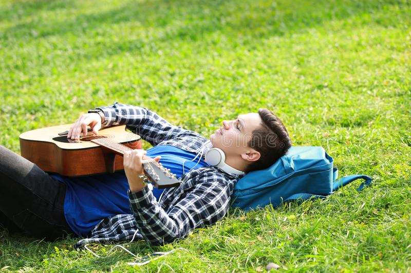 Young man playing guitar while lying on green grass in park royalty free stock photos