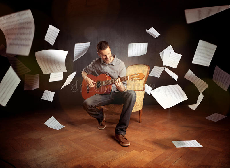 Young man playing guitar with sheet music flying around him royalty free stock photos