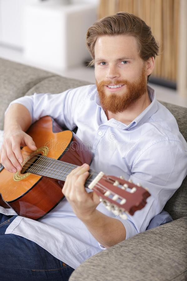 Young man playing guitar on sofa stock images