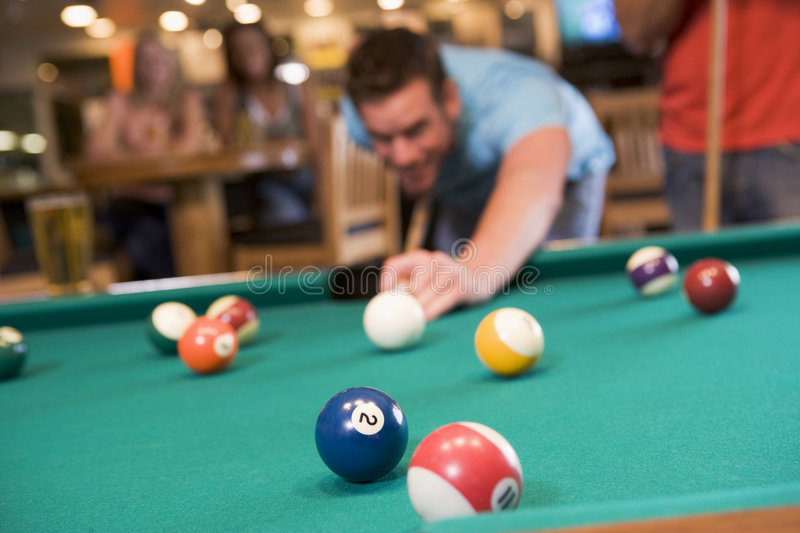 Young man playing pool in a bar. (focus on pool table royalty free stock photo