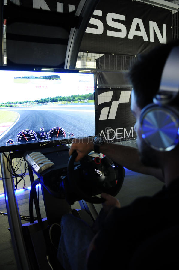 Young Man Playing Race Cars. Modern driving simulator for PS4. In 2014, PlayStation Portugal and GT Academy launched a challenge to find another pilot who can royalty free stock image