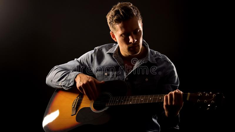 Young man playing romantic ballad on guitar, acoustic performance, concert royalty free stock photos