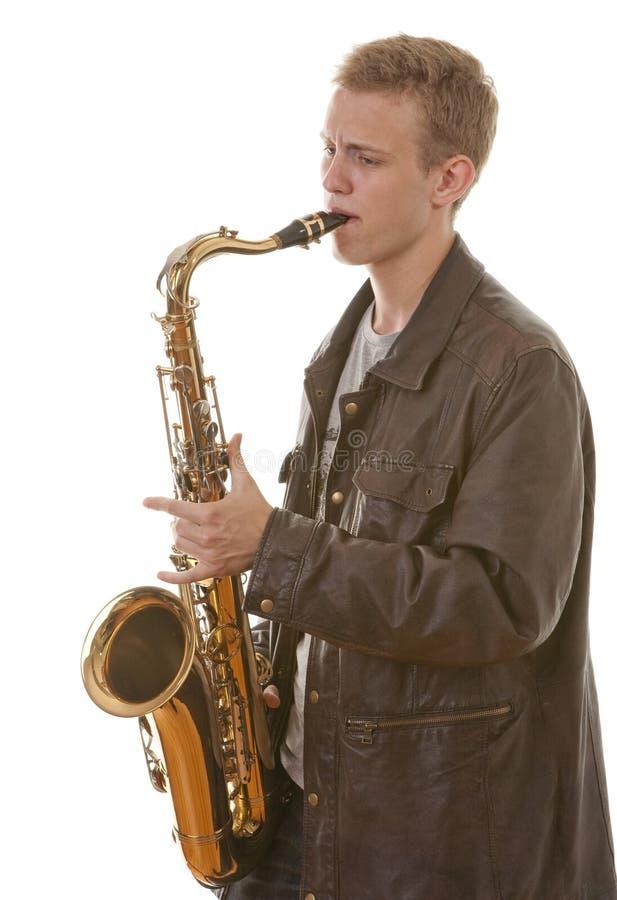 Young man playing saxophone royalty free stock image
