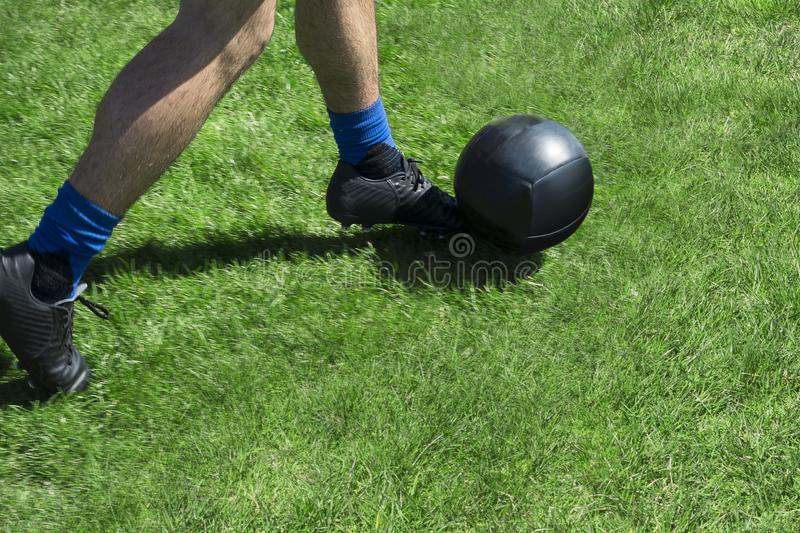 soccor player kicking abll of a green grassy field with black kelletts and balck ball royalty free stock photo