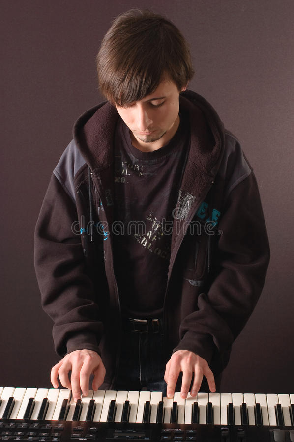Young man playing on a synthesizer royalty free stock photos