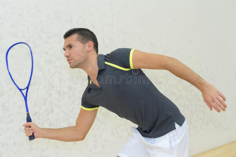 Young man playing tennis indoors royalty free stock image
