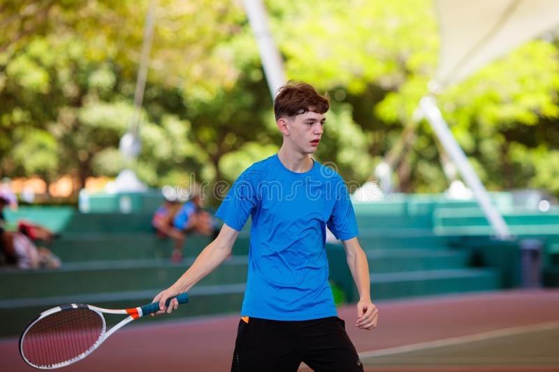 Young man playing tennis on open court royalty free stock photos