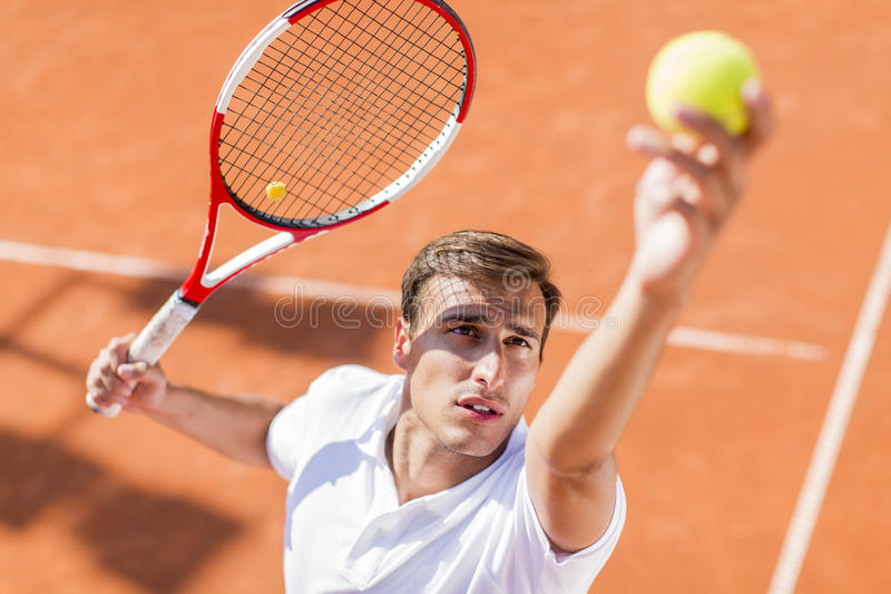 Young man playing tennis stock images