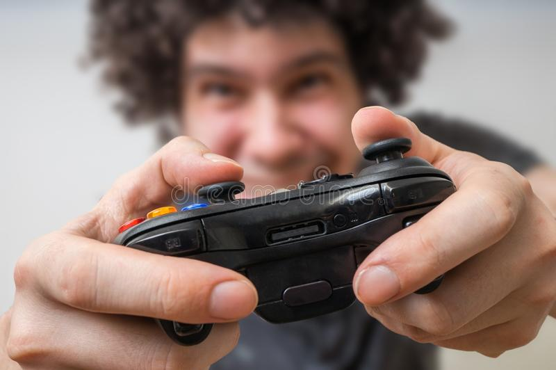 Young man is playing video games and holds joystick or controller stock images