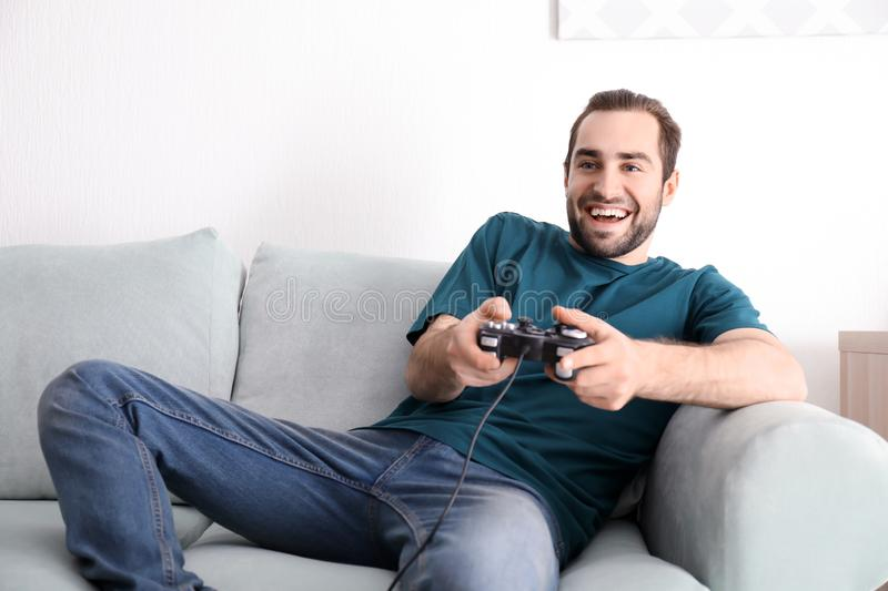 Young man playing video games at home royalty free stock photos