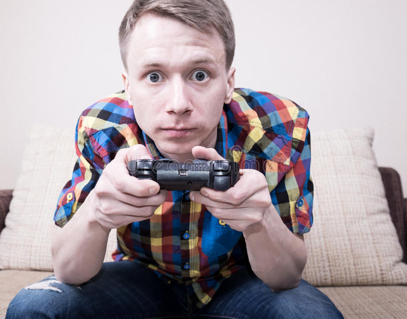 Young man playing. Video games sitting at sofa and holding remote controller stock photo