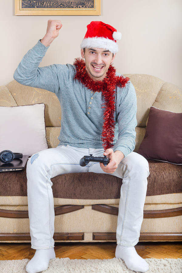 Young man playing video games with wireless Bluetooth joystick royalty free stock image