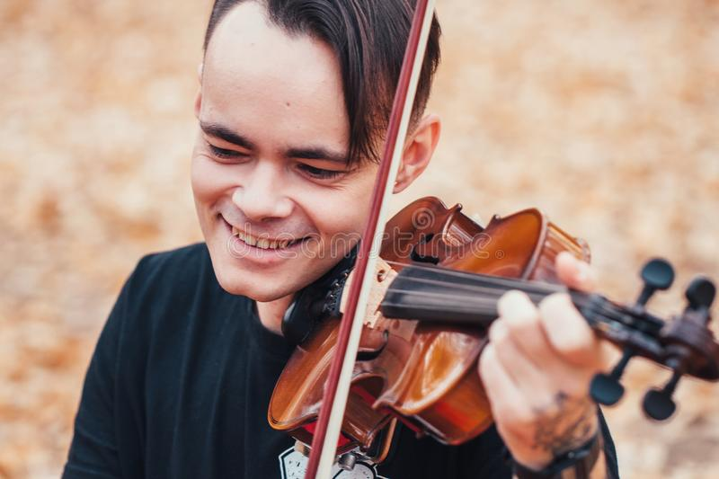 Young man playing violin in the autumn forest stock image