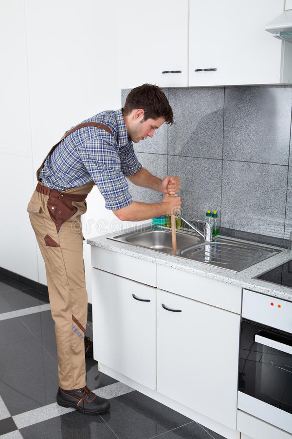 Young Man With Plunger. Young Handsome Man Using Plunger In Kitchen Sink royalty free stock image