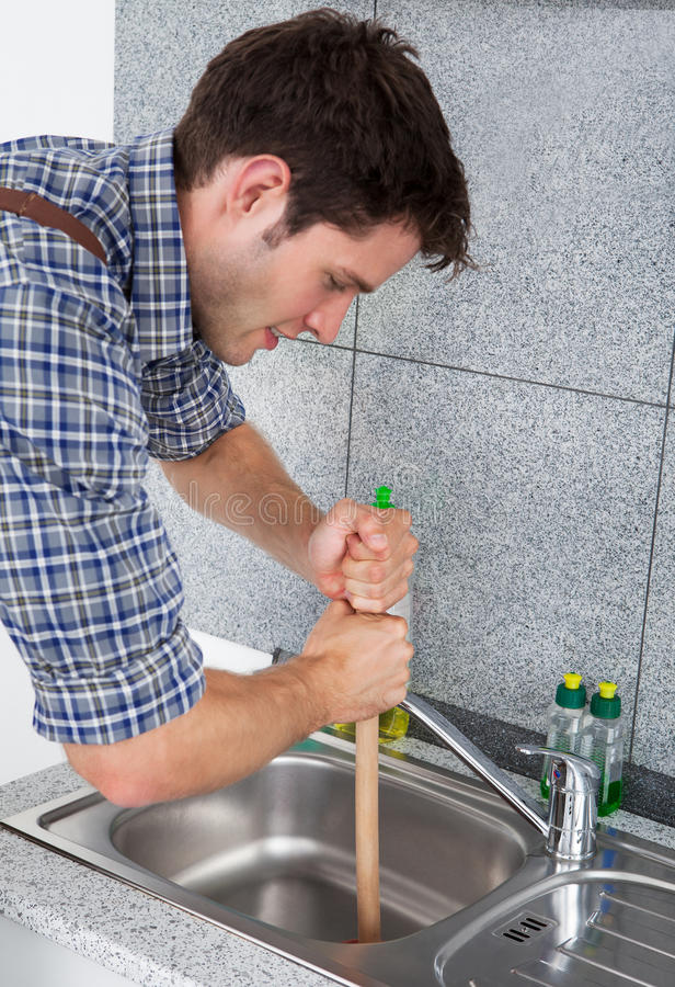 Young Man With Plunger. Young Handsome Man Using Plunger In Kitchen Sink stock image