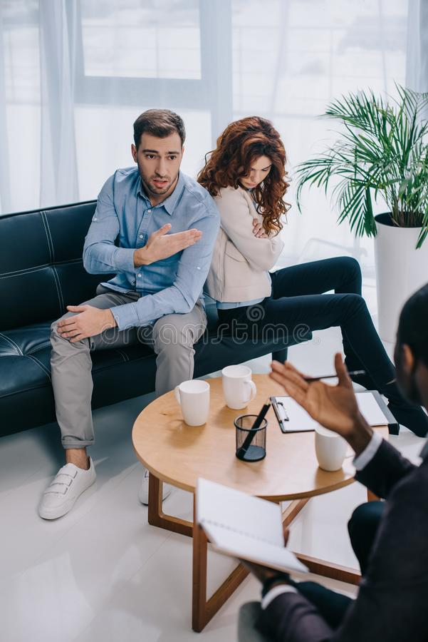 Young man pointing at girlfriend and talking to african. American counselor royalty free stock photo