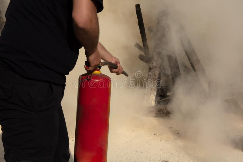 Young man pointing a fire extinguisher forwards. Young man pointing a powder type fire extinguisher forwards towards the fire in a serious situation stock images