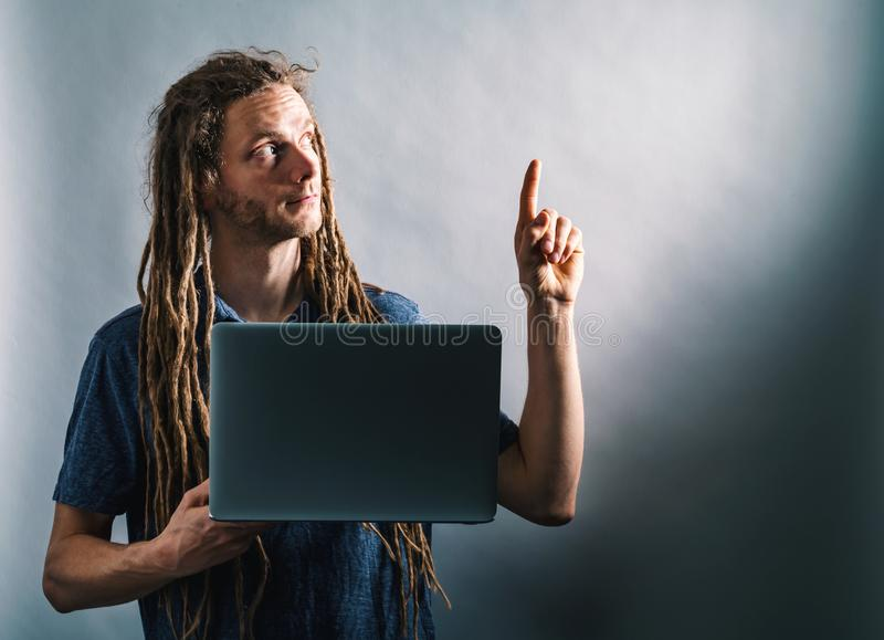 Young man pointing up while using a laptop stock photos