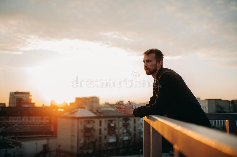 Young man is pondering on terrace of roof against background of cityscape at sunset. stock photos