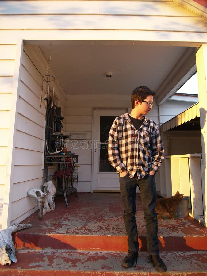 Young Man on a Porch. Portrait of a young man standing on the front porch of a house royalty free stock photo