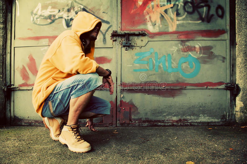 Young man portrait, graffiti wall. Young man portrait in hooded sweatshirt / jumper on grunge graffiti wall royalty free stock photos
