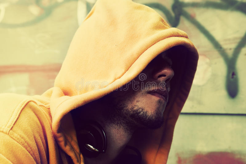 Young man portrait, graffiti wall. Young man portrait in hooded sweatshirt / jumper on grunge graffiti wall stock photos
