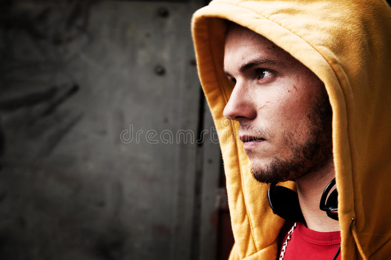 Young man portrait, grunge wall. Young man portrait in hooded sweatshirt / jumper on grunge graffiti wall royalty free stock image