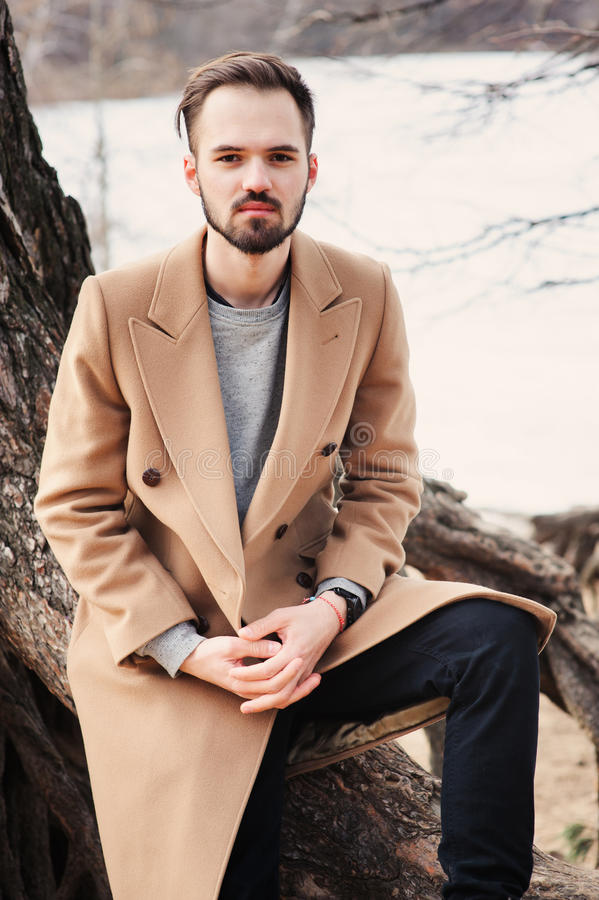 Young man portrait on the walk in autumn forest in beige coat royalty free stock images