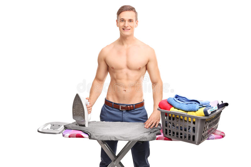 Young man posing behind an ironing board. Young shirtless man posing behind an ironing board with a basket full of clothes on it isolated on white background stock image
