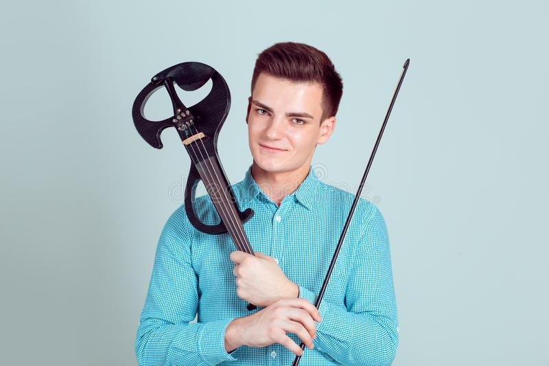 Young man holding violin and fiddlestick. Young man posing holding modern violin and arc smiling crossing arms in studio isolated light blue wall background stock images