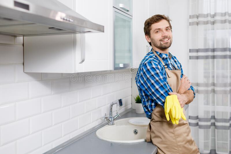Young Man Posing After Intense Household Work. Contented young man posing leaning at the kitchen table top after intense household work stock photography